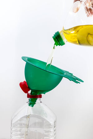 old frying oil pouring into another bottle with a green funnel