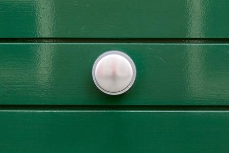 on a green painted door with a steel door handle photo