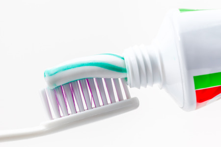 an toothbrush with toothpaste with green and white colors photo