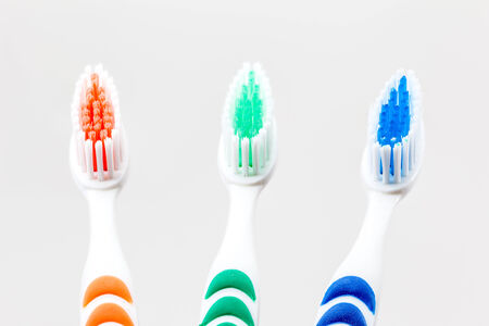 three toothbrushs with differend kind of colors photo