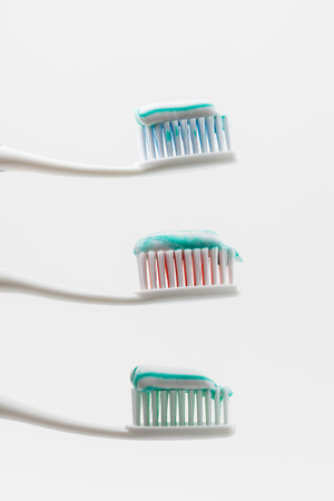 two toothbrushs with toothpaste with green and white colors between them photo