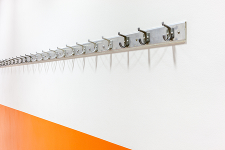 in the hallway of the school hangs a coat rack on the wall