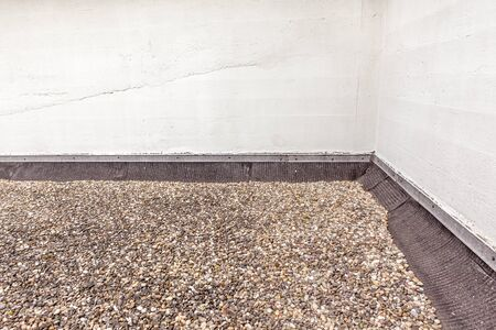 flat roof filled with boulders on the roofing Stock Photo