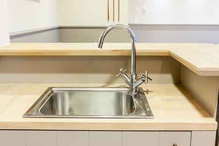in the kitchen there is a sink built into the wood sheet 写真素材
