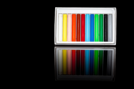oil pastels: twelve oil pastels on a black background with reflection Stock Photo