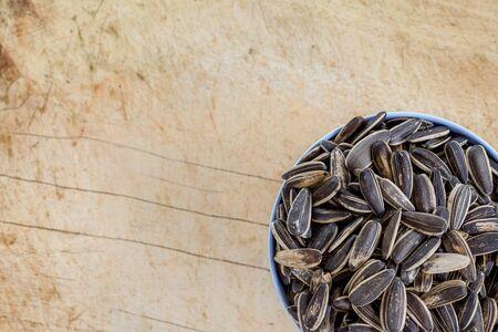 semillas de girasol: cuenco lleno de semillas de girasol en una placa de madera