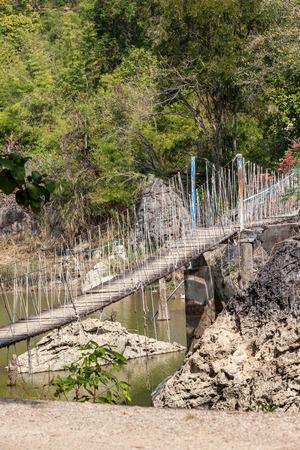 suspenso: sobre el agua entre dos rocas cuelga de un puente colgante Foto de archivo