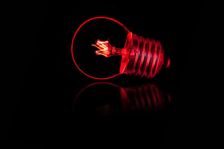 object glass: on a black polished tile light a red burning light bulb