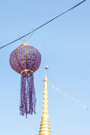 cabel: a fabric ball decoration with garlands on a steel cabel next to the temple