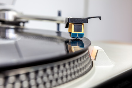 converts: an arm of a record player with a steel needle that converts sound waves into music