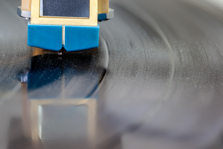 vibrations: an arm of a record player with a steel needle that converts sound waves into music