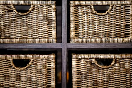 rattan mat: handles wicker baskets on wooden rack Stock Photo
