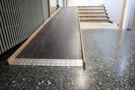 al lado de las escaleras, hay un puente de madera para sillas de ruedas