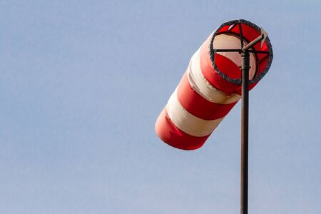 moderate: Frayed windsock in moderate wind against blue sky