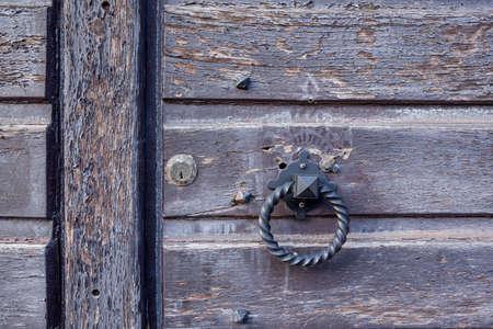 door knocker: on this wooden door you find an Door knocker