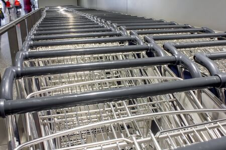 several luggage cart at the airport in the departure hall Banco de Imagens