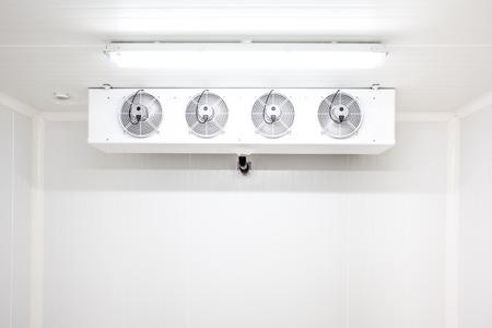 een lege industriële koelkast op de kamer met vier fans
