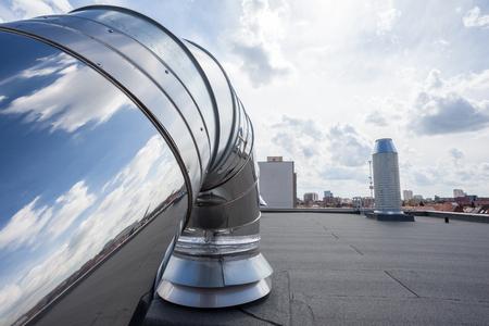 inox Schoorsteen op het platte dak in de stad Stockfoto