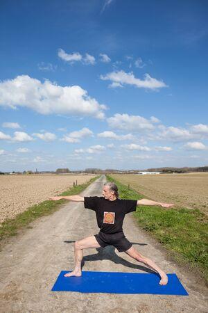 virabhadrasana: on an sunny day this man enjoys Virabhadrasana yoga in nature