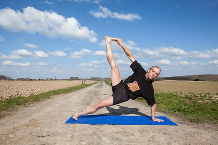 meditative: on an sunny day this man enjoys Vasisthasana or Side Plank Pose yoga in nature Stock Photo
