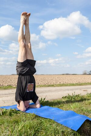 hasta: on an sunny day this man enjoys Mukta Hasta Sirsasana yoga in nature