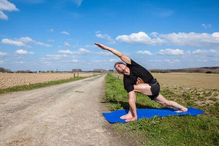 utthita: on an sunny day this man enjoys Utthita Parsvakonasana yoga in nature