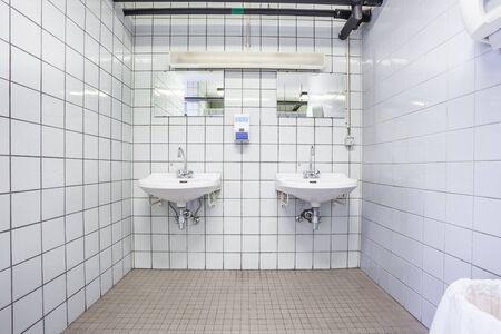 public restroom: in an public restroom hangs on an wall two white sink