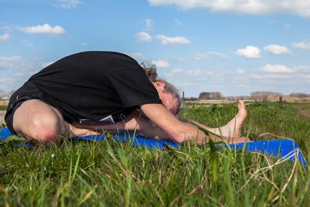 janu: on an sunny day this man enjoys Janu Sirsasana yoga in nature Stock Photo