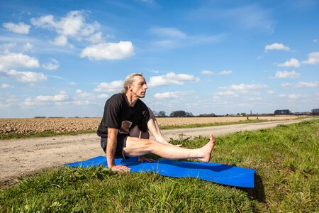 hasta: on an sunny day this man enjoys eka hasta bhujasana yoga in nature Stock Photo