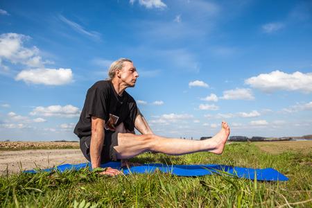 eka: on an sunny day this man enjoys eka hasta bhujasana yoga in nature Stock Photo