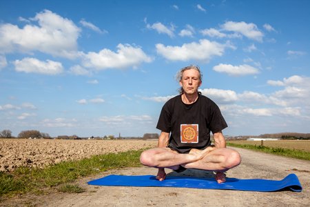 on an sunny day this man enjoys Lotus Pose yoga in nature Stock Photo