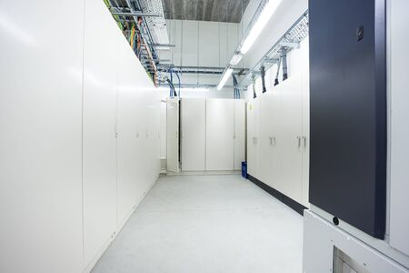 in the basement of an industrial building there is an room with electrical cabinets