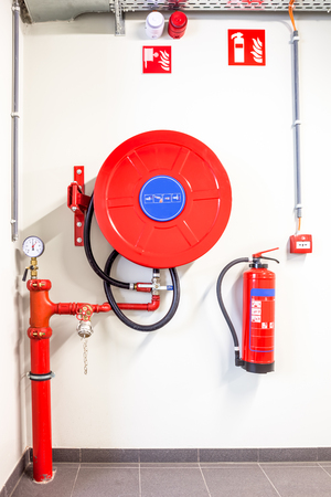 un tuyau d'incendie accroché au mur et un extincteur à poudre