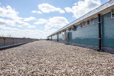 Er zijn kiezelstenen op het dak naast een stenen muur