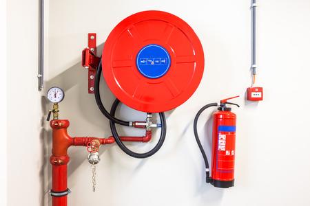 Un tuyau d'incendie accroché au mur et un extincteur à poudre Banque d'images - 60661813