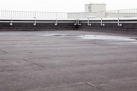 een plat dak met dakbedekking en omheiningen