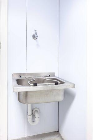inox: in an public restroom hangs on an wall of an inox sink