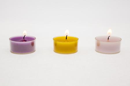 verschillende kleuren thee licht kaarsen met witte achtergrond