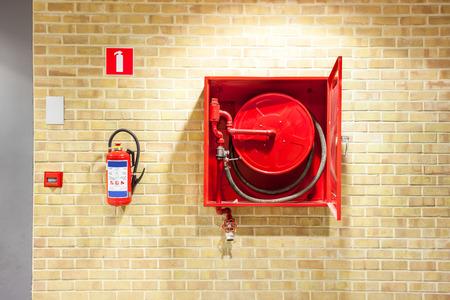 階段の壁に掛かっている消防用ホース 写真素材