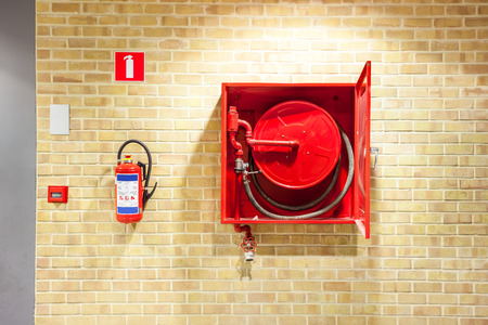 an fire hose hanging on the wall in an staircase Stock Photo