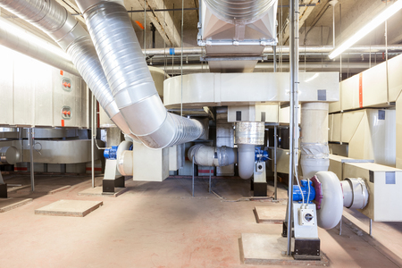 exhaust system: under the roof of a large building, there is a technical room with exhaust system Stock Photo