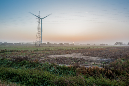 electricity pole: sunrise with fog and windmill next to an electricity pole Stock Photo