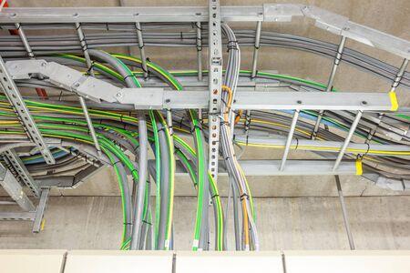 cables electricos: Los cables eléctricos con cable de tierra amarilla y verde que sale de un cuadro eléctrico Foto de archivo