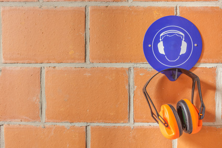 hearing protection: an blue placard for compulsory wearing of ear protection and a hearing protector on the hook Stock Photo