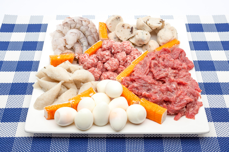 on a decorated plate lies suki with shrimp, eggs, cut meat, raw meat, crab