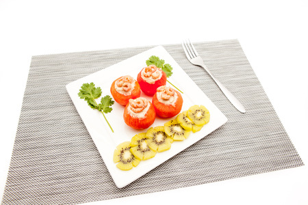 an white board with shrimp and tomato and to decorate some slices of kiwi fruit