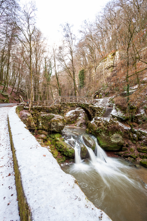 benelux: deep in the forest there is a small waterfall in switzerland in Luxembourg whit snow