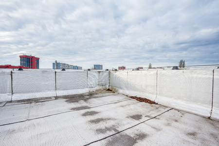 an flat roof with roofing and fencing Фото со стока