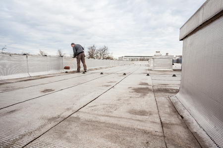bitumen felt: an flat roof with roofing and fencing Stock Photo