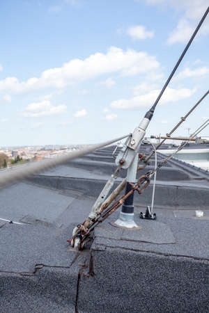 An antenna is attached to a flat roof with iron cables